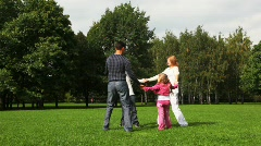 Family with boy and girl drives a round dance on field in park Stock Footage