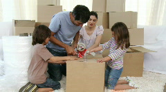 Parents and children moving house packing boxes - stock footage