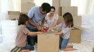 Parents and children moving house packing boxes Stock Footage