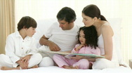 Family reading a book on bed Stock Footage