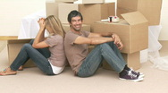 Tired couple sitting on floor after buying house Stock Footage