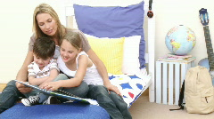 Mother reading a book with her children Stock Footage