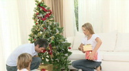 Family playing with presents around the Christmas tree at home Stock Footage
