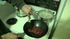 Man hands cooking hamburger in stir fry wok Stock Footage