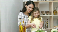 Mother and daughter cooking a salad Stock Footage