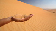 Sand running through fingers of single hand Stock Footage