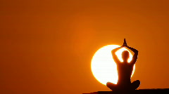 woman making yoga at sunset huge sun - stock footage