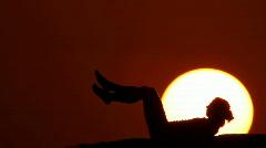 Woman crunching at sunset huge sun Stock Footage
