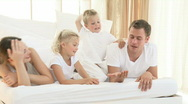 Happy young family playing in bed Stock Footage