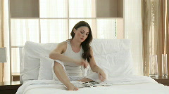 Stock Video Footage of Woman studying her budget sitting on the bed