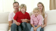 Family watching television at home celebrating a success in a match Stock Footage