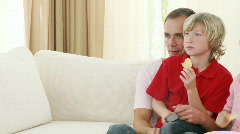 Family watching television and eating crisps at home Stock Footage