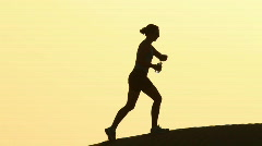 Woman walking up hill drinking Stock Footage
