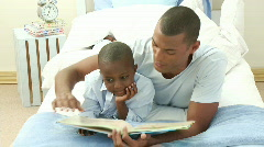 Afro-American little boy reading a book with his father in bed - stock footage