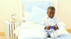 Afro-American little kid playing video games in hid bedroom Stock Footage