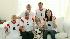 Extended Family with grandparents on the sofa watching Football Stock Footage