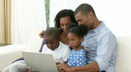 Afro-American family using a laptop on the sofa Stock Footage