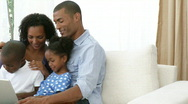 Stock Video Footage of Panorama of Afro-American family using a laptop on the sofa