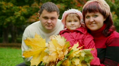 Family of three person with autumn leafs in park Stock Footage
