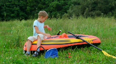 Boy puts on a life jacket sitting on an inflatable rubber dinghy Stock Footage