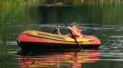 Boy turn round on an inflatable boat on lake Stock Footage