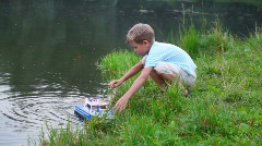 Boy get toy ship from water Stock Footage