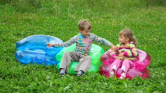 Boy and girl sitting on inflatable armchairs Stock Footage
