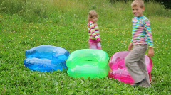 Boy and girl walking around inflatable armchairs Stock Footage