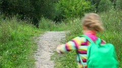 Little girl with rucksack running in park from camera Stock Footage