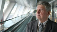 Senior man in suit moving up on escalator Stock Footage
