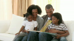 Afro-American parents and children reading a book in the living-room - stock footage