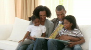 Stock Video Footage of Afro-American parents and children reading a book in the living-room