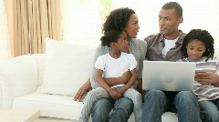 Panorama of Afro-American family using a laptop on the sofa - stock footage