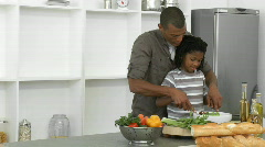 Afro-American father and son preparing a salad at home - stock footage