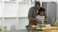 Afro-American father and son preparing a salad at home Stock Footage