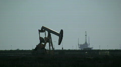 Pumpjack With Oil Rig In Background - stock footage