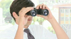 Young Businessman looking through binoculars Stock Footage