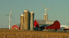 Farm buildings with windturbine on harvested fields in fall - stock footage