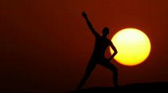 Woman doing gymnastics at sunset huge sun 2 Stock Footage