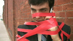 Businessman caught in red tape. Closeup. Stock Footage