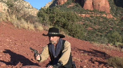 Cowboy aims gun and fires in red rocks Stock Footage