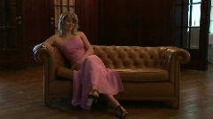 HD1080i Young blonde woman in evening dress sitting on couch and looking towards Stock Footage