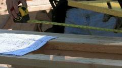 Carpenter measuring according to blueprints Stock Footage