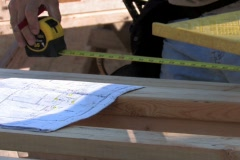 Carpenter marking wood according to blueprints Stock Footage