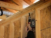 Electrician drilling hole in wooden studs Stock Footage