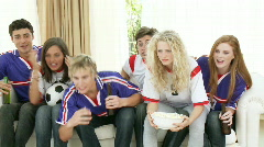 Teenagers watching a football match at home Stock Footage