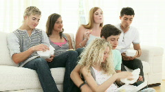 Teenagers watching television and eating sandwitches Stock Footage