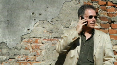 Businessman on cell against old wall Stock Footage