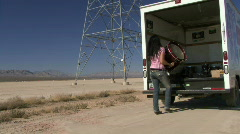 Female lifting drum out of a van in a desert Stock Footage