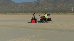 Male and female playing music in desert and walking away Stock Footage
